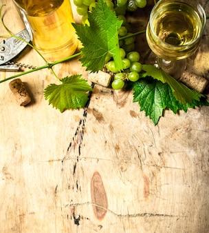 Weißwein mit einer rebe auf holztisch.