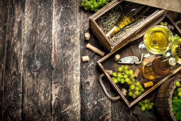Weißwein mit frischen trauben auf altem tablett.