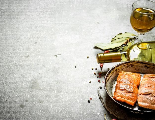 Weißwein mit gegrilltem lachsfilet auf dem steintisch.