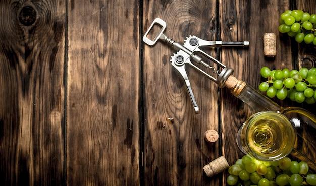 Weißwein mit korkenzieher und traubenzweigen. auf einem holztisch.