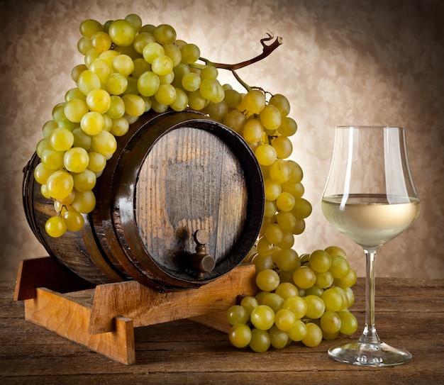Weißwein mit trauben und fass.