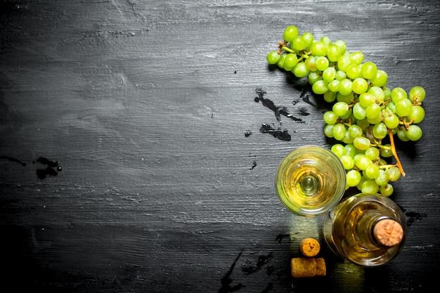 Weißwein mit traubenzweigen. auf einem schwarzen hölzernen hintergrund.