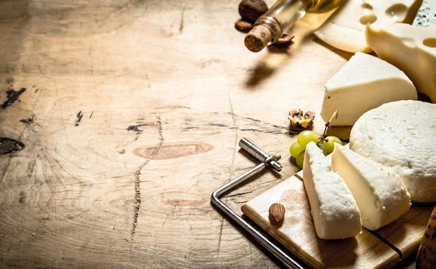 Weißwein mit verschiedenen käsesorten auf holztisch.