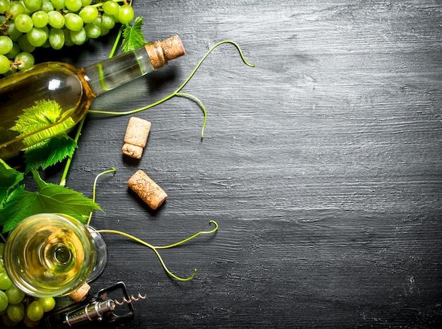Weißwein mit weinstock. auf einem schwarzen hölzernen hintergrund.