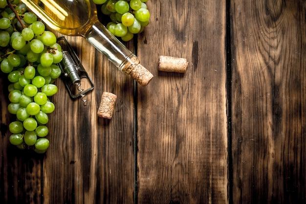 Weißwein mit zweigen der weißen trauben auf holztisch.