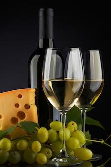 Weißwein und käse auf schwarz