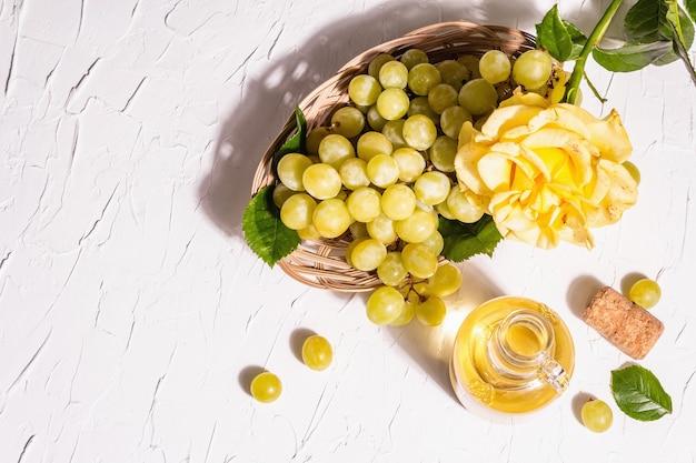 Weißwein und traube in einem weidenkorb. frische früchte und rosenblüte. ein trendiges hartes licht, dunkler schatten, draufsicht
