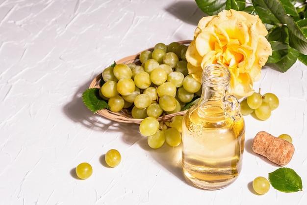 Weißwein und traube in einem weidenkorb. frische früchte und rosenblüte. ein trendiges hartes licht, dunkler schatten, kopierraum