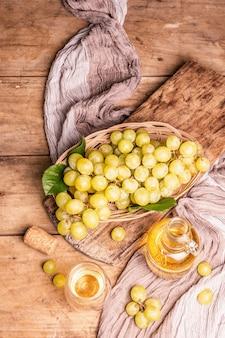 Weißwein und traube in einem weidenkorb. frisches obst, glas und flasche. alte holzbretter hintergrund, ansicht von oben