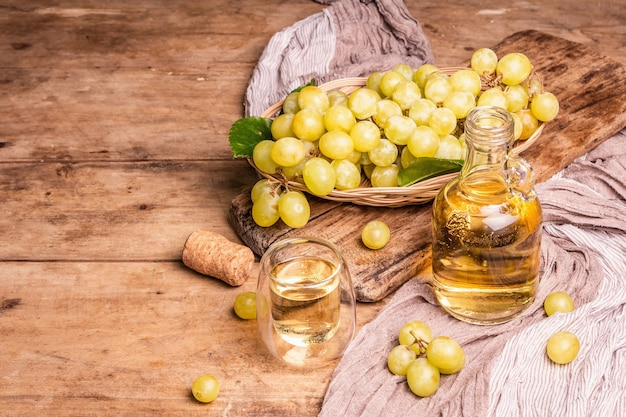 Weißwein und traube in einem weidenkorb. frisches obst, glas und flasche. alte holzbretter hintergrund, kopienraum