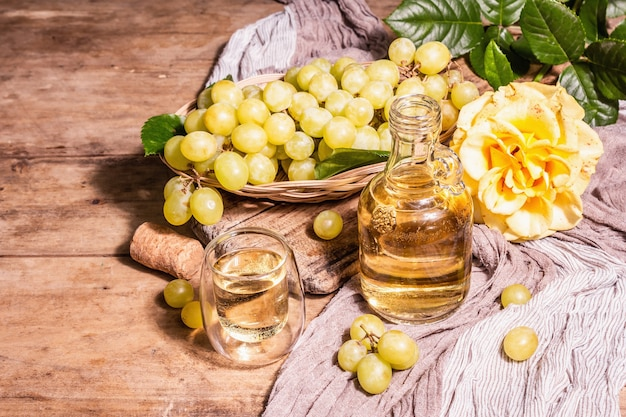 Weißwein und traube in einem weidenkorb. frisches obst, glas und flasche. modernes hartes licht, dunkler schatten. alte holzbretter hintergrund, kopienraum