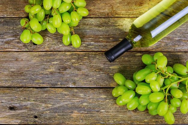 Weißwein und trauben wein und trauben in der weinleseeinstellung mit holztisch
