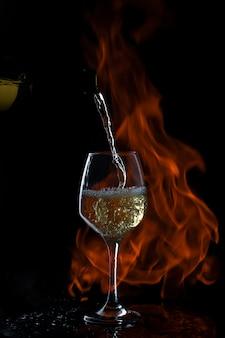 Weißwein wird in glas mit langem stiel in dunklem hintergrund mit feuer gegossen