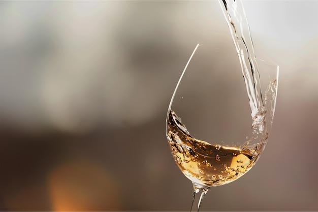 Weißwein wird in weinglas gegossen, nahaufnahme