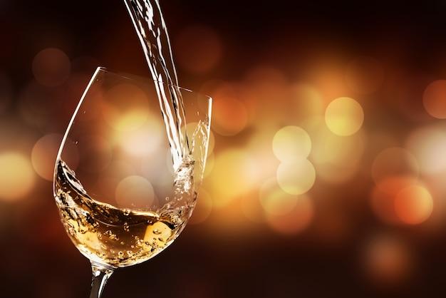 Weißwein wird ins weinglas gegossen