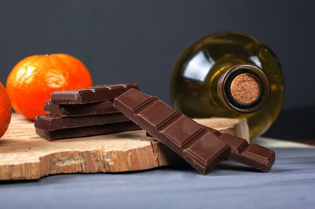 Weißweinflasche mit stücken milchschokolade und mandarinen auf einem hölzernen waldregal auf grauer dunkelheit