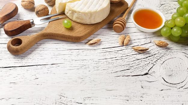 Weißweinflasche, -traube, -honig, -käse und -weinglas auf weißem hölzernem brett