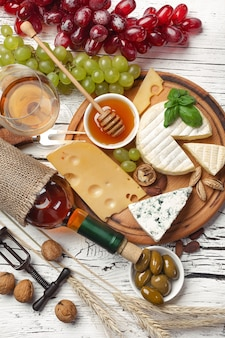 Weißweinflasche, traube, honig, käse und weinglas auf weißem holzbrett. draufsicht mit kopienraum.
