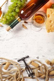 Weißweinflasche, traube, honig, käse, weinglas mit korkenzieher, korken und seil auf weißem holzbrett. draufsicht mit kopienraum.