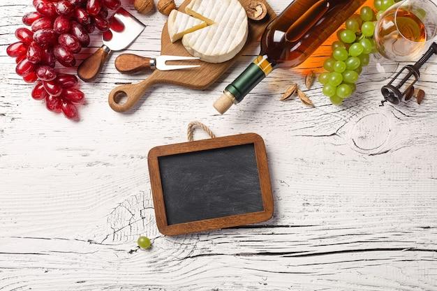 Weißweinflasche, traube, honig, käse, weinglas und kreidetafel auf weißem holzbrett. draufsicht mit kopienraum.
