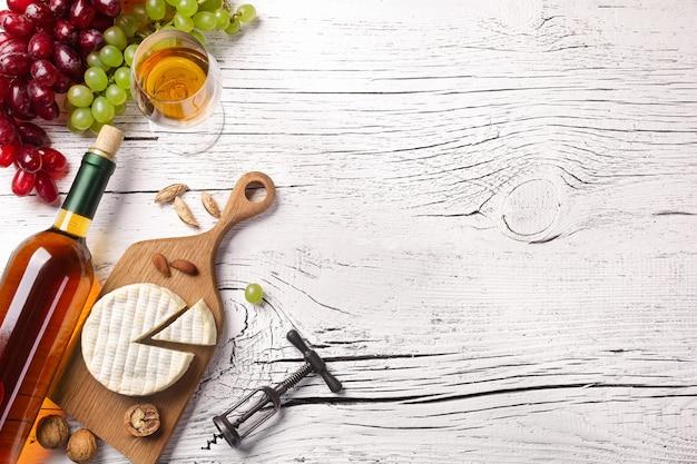 Weißweinflasche, traube, käse und weinglas auf weißem holzbrett. draufsicht mit kopienraum.