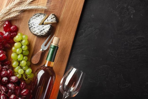 Weißweinflasche, weintraube, käse, weizenähren und weinglas auf holzbrett und schwarzem hintergrund. draufsicht mit kopienraum.