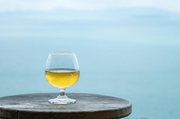 Weißweinglas der nahaufnahme auf dem tisch auf seeansichthintergrund