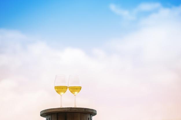 Weißweinglas der nahaufnahme zwei auf dem tisch an der terrasse auf himmel
