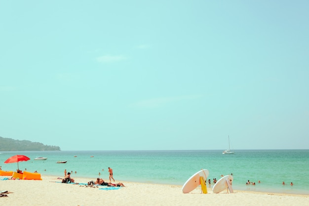 Weit entferntes bild schoss und unscharfes gesicht von mengenleuten auf sandstrand