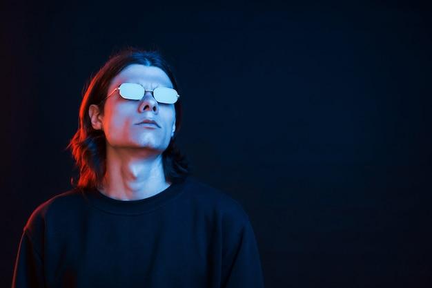 Weit weg schauen. studioaufnahme im dunklen studio mit neonlicht. porträt eines ernsten mannes