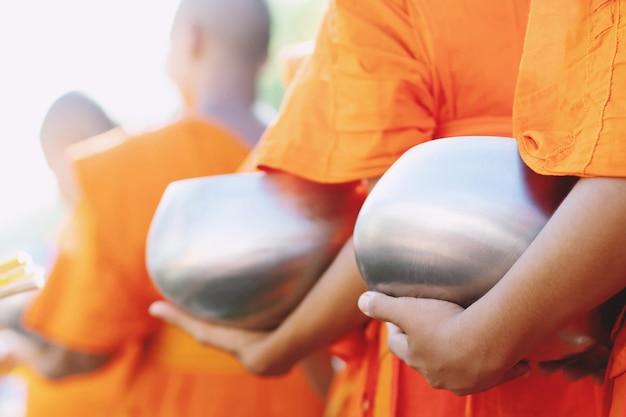 Weitere mönche mit händchenhalten geben eine almosenschale, die am morgen im buddhistischen tempel aus den opfergaben kam