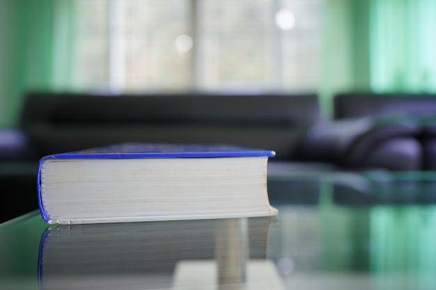 Weitwinkel-nahaufnahme des buches mit unscharfem wohnzimmerhintergrund