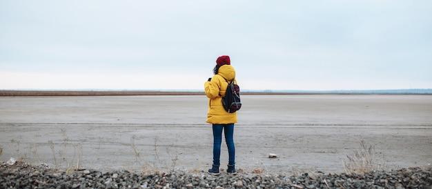 Weitwinkel-rückansicht einer jungen touristin mit einem rucksack, der auf einer seitenstraße zwischen einem riesigen, leeren wintertal-tiefland läuft. frau, die gelbe jacke und roten hut trägt. trampen, reisekonzept.