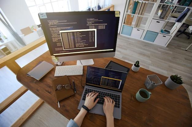 Weitwinkel über ansicht bei weiblichen händen, die auf tastatur während des codierens am arbeitsplatz im modernen büroinnenraum tippen, kopieren raum