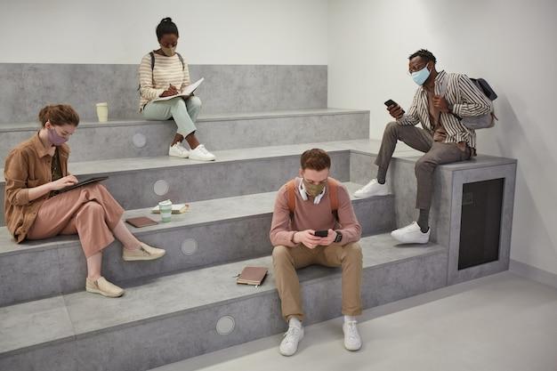 Weitwinkelansicht auf verschiedene schülergruppen, die masken tragen, während sie sich in der modernen schullounge mit sozialer distanzierung entspannen