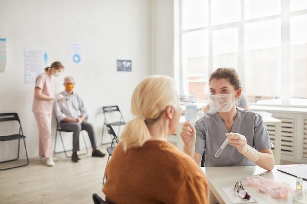 Weitwinkelansicht bei junger ärztin, die covid-tests in einer klinik oder einem impfzentrum durchführt, kopierraum