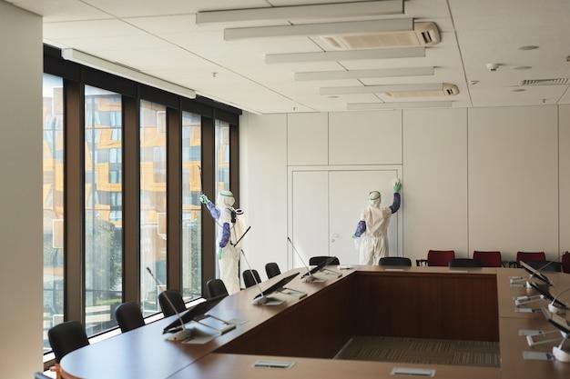 Weitwinkelansicht bei zwei sanitärarbeitern, die hazmat-anzüge tragen, die den konferenzraum im büro desinfizieren,