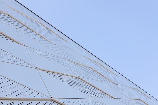 Weitwinkelansicht der metallwand mit dreieckigem muster und runden öffnungen gegen blauen himmel