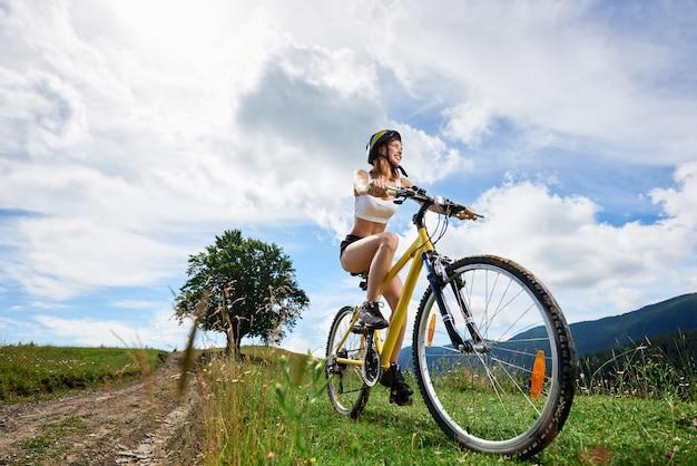 Weitwinkelansicht der radfahrerin der athletenfrau, die auf gelbem fahrrad auf einer ländlichen spur reitet