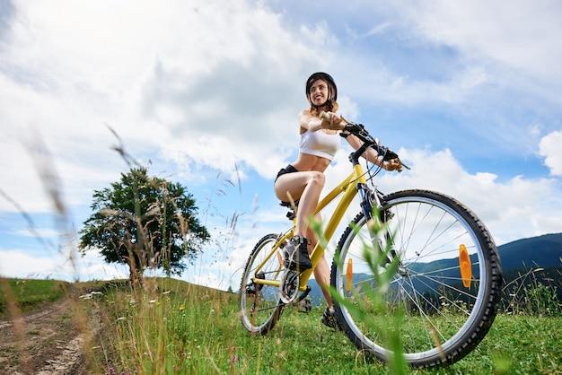 Weitwinkelansicht der sportlichen fahrerin, die auf gelbem fahrrad auf einer ländlichen spur in den bergen radelt