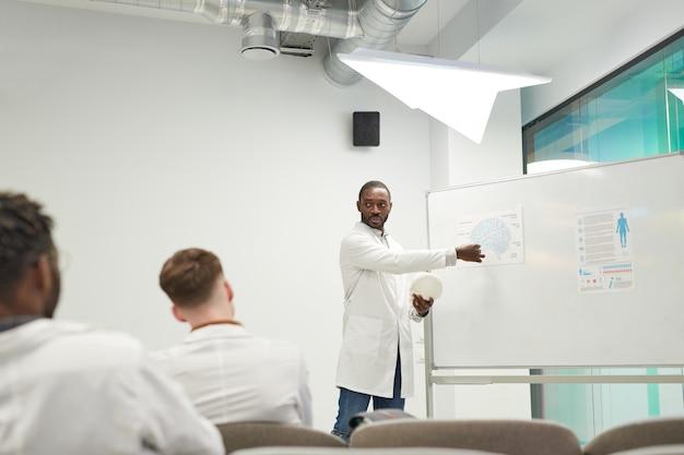 Weitwinkelansicht des afroamerikanischen mannes, der am whiteboard steht, während er ein seminar über medizin im college hält, kopierraum