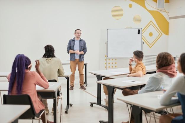 Weitwinkelansicht eines reifen männlichen lehrers, der der klasse junger schüler in der modernen schule einen vortrag hält, kopierraum