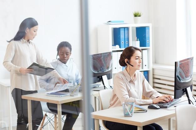 Weitwinkelansicht im callcenter-innenraum mit weiblichen bedienern, die headsets am arbeitsplatz tragen