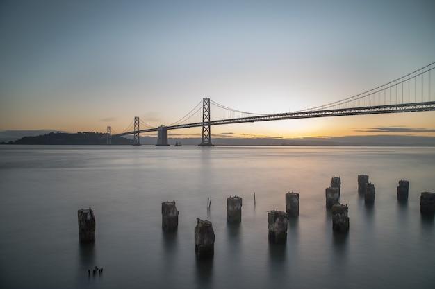 Weitwinkelaufnahme der bay bridge auf dem gewässer während des sonnenaufgangs in san francisco, kalifornien
