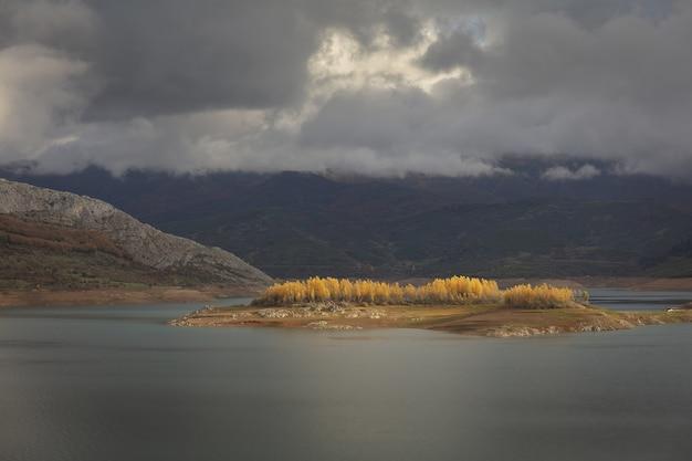 Weitwinkelaufnahme des riano-wasserreservoirs in spanien unter einem bewölkten himmel