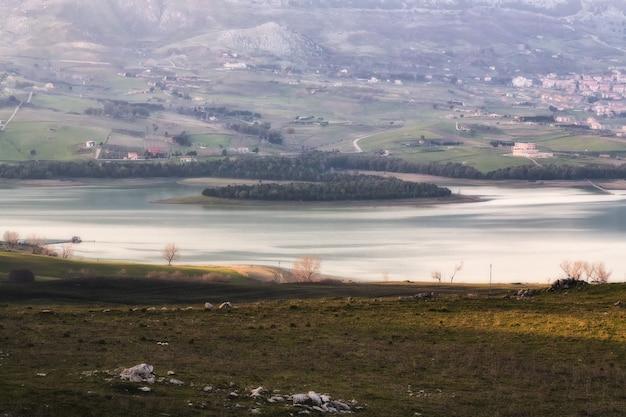Weitwinkelaufnahme des schönen meeres, umgeben von grünen bäumen und nebelbedeckten gebäuden