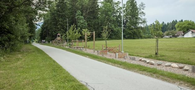 Weitwinkelaufnahme einer fahrradstraße und eines spielplatzes in der nähe von hohen bäumen