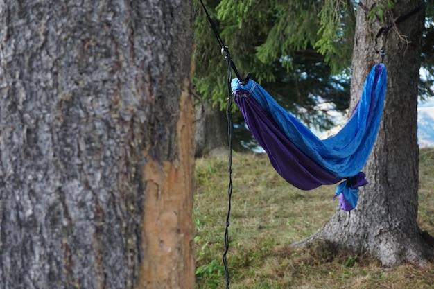 Weitwinkelaufnahme einer hängematte, die zwischen zwei bäumen in einem grasbewachsenen gelände auf einem berg hängt