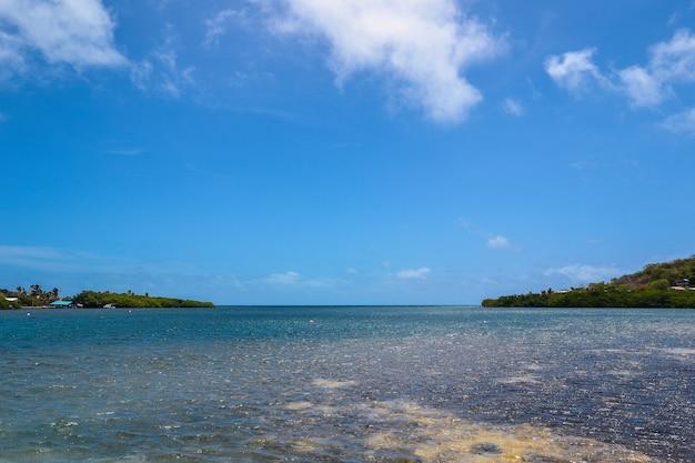 Weitwinkelaufnahme einer schönen ansicht des ozeans mit einem bewölkten blauen himmel