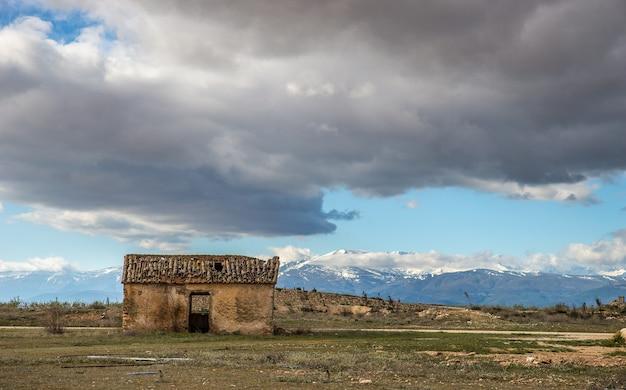 Weitwinkelaufnahme eines alten hauses auf einem berg unter einem bewölkten himmel